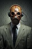 image of gas mask  - Man wearing vintage gas mask and headphones listening to music - JPG