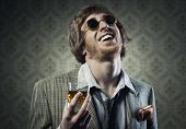 stock photo of unhealthy lifestyle  - Funny guy holding a glass of whisky and posing against vintage wallpaper - JPG