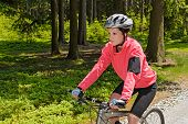 stock photo of bike path  - Woman mountain biking in forest on sunny day cycling path - JPG