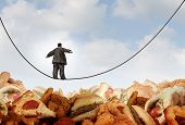 stock photo of obese  - Overweight diet danger concept as an obese man walking on a tightrope high wire over mountains of greasy unhealthy junkfood as a metaphor for dieting risk and the challenges of eating disorders resulting in obesity - JPG