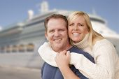 stock photo of passenger ship  - Young Happy Couple Hugging On The Dock In Front of a Cruise Ship - JPG