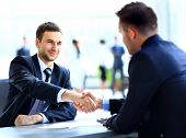stock photo of contract  - Two business colleagues shaking hands during meeting - JPG