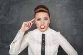 stock photo of sarcasm  - Beautiful young fashion woman gesturing with finger to her head - JPG