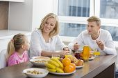 Happy family of three having breakfast at table