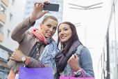 pic of two women taking cell phone  - Female friends with shopping bags taking photos through mobile phone - JPG
