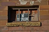 No Trespassing Sign over Barred Window
