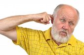 stock photo of goofy  - goofy bald senior man picking his ear with index finger - JPG