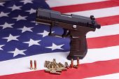 stock photo of ammo  - A conceptual image of a pistol and ammo on a US flag.