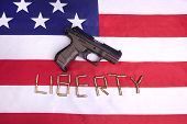 picture of ammo  - A concept image of a pistol on a US flag and the ammo spelling out the word liberty - JPG