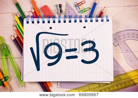 Square root of three on notepad against students desk
