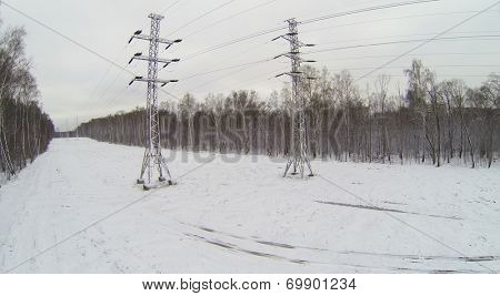 Power line poles in snowy forest near the city, aerial view