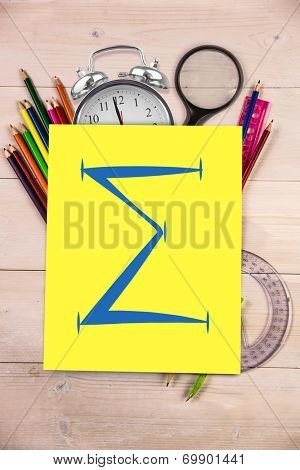 Sum symbol against students desk with yellow page