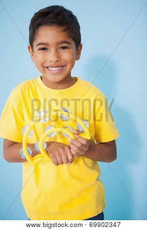 Cute little boy playing the tambourine in classroom at the nursery school