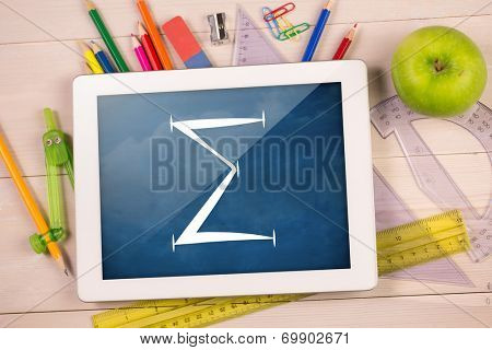 Composite image of digital tablet on students desk showing sum symbol