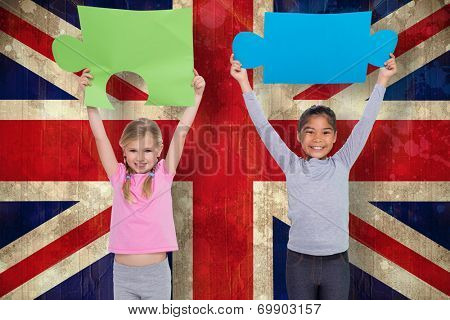 Elementary pupils holding jigsaw pieces against union jack flag in grunge effect