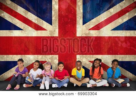 Cute pupils smiling at camera with books against union jack flag in grunge effect