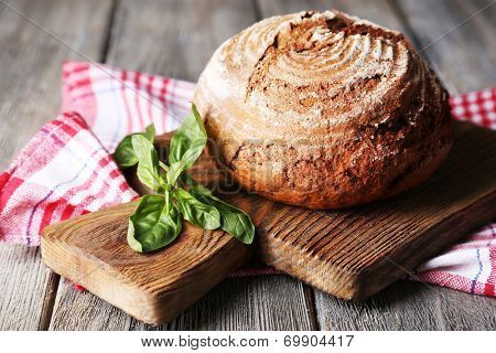 Fresh baked bread and fresh basil on cutting board, on wooden background