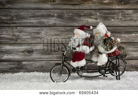 Funny Wooden Christmas Background With Two Santa Claus On A Bicycle Making Xmas Shopping.