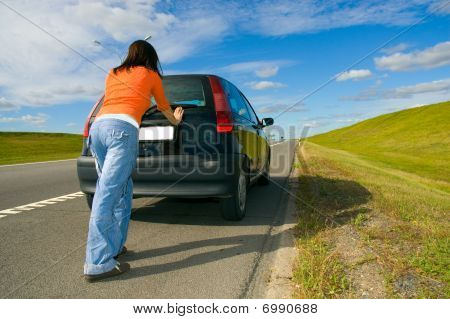 woman pushing a car