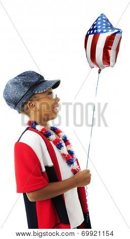 Profile of a young elementary girl wearing red, white and blue, happily looking at the stars and stripes on the balloon she holds.  On a white background.