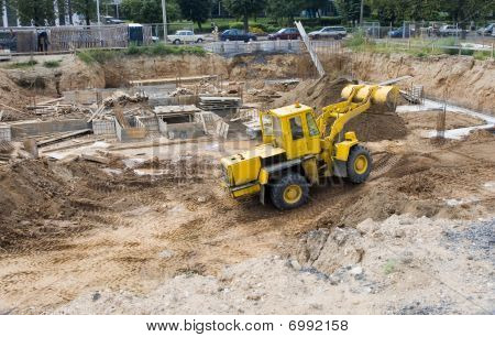 yellow bulldozer digging a ditch on the rack