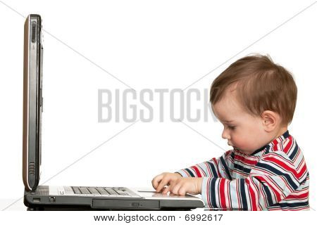 Little Boy Is Working With A Laptop