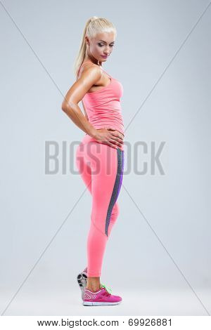 Beautiful fitness model posing on gray background