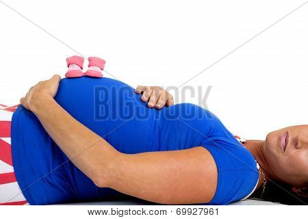 Pregnant Model Laying Down With A Pair Of Pink Baby Booties On Her Belly