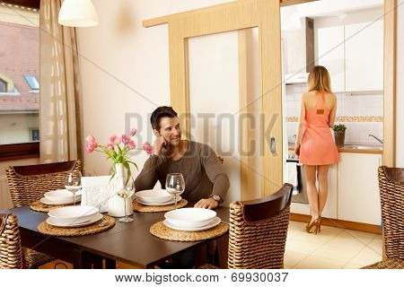 Young couple waiting for dinner guests at home, woman in kitchen cooking.