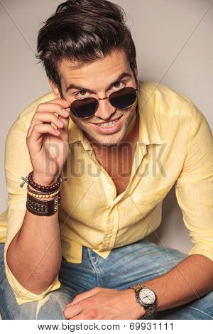 fashion man looks up and takes off his sunglasses, laughing to the camera