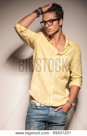 relaxed casual fashion man passing his hand through his hair in studio, looking away from the camera