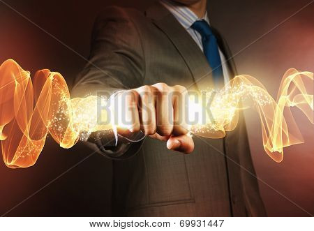 Close up of businessman hand holding light ray in fist
