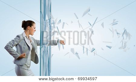 Young determined businesswoman breaking glass with karate punch