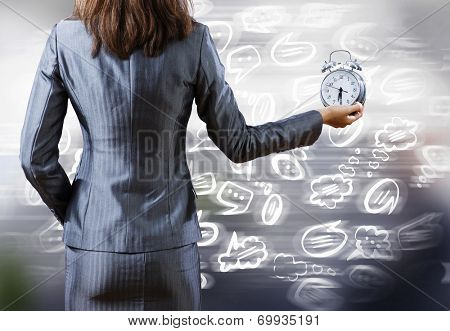 Rear view of businesswoman holding old alarm clock