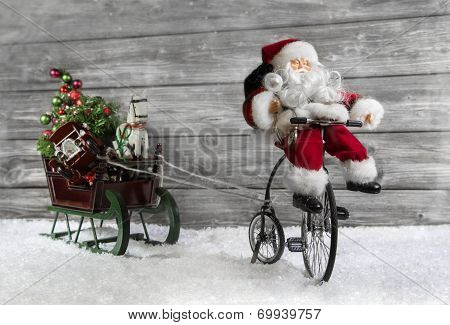 Funny Christmas Greeting Card With Santa On A Bike Pulling A Slide.