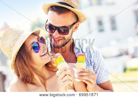 A picture of a lovely couple eating ice-cream in the city