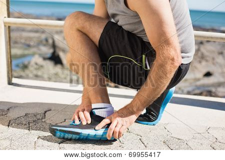 Fit man gripping his injured ankle on a sunny day