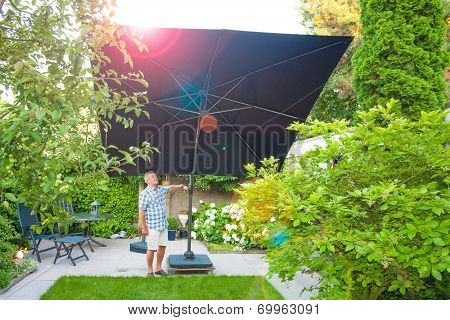 Man Setting Up A Parasol In The Backyard