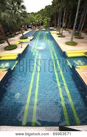 A big swimming pool with clear water and seats in water in the Nong Nooch tropical botanic garden ne