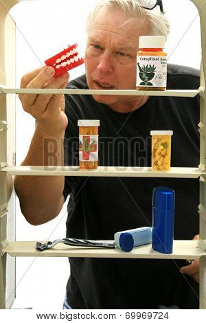 A man a pair of chattering teeth in front of his bathroom Medicine Cabinet. Chattering teeth have been used to prank and supply humor and jokes to people around the world for decades.