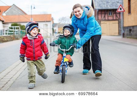 Young Mother Teaching Her 2 Years Old Little Son To Ride A Bike