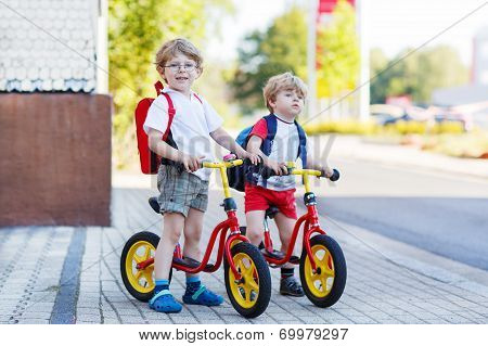 Two Little Siblings Children Having Fun On Bikes In City, Outdoors.