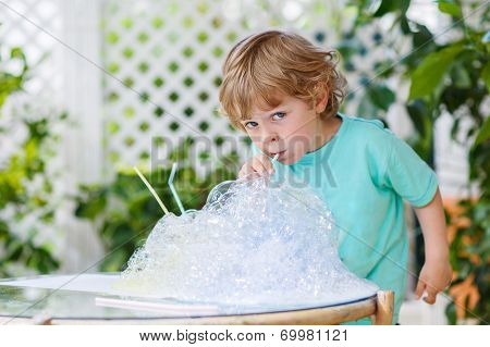 Happy Little Boy Making Experiment With Colorful Water And Soap Bubbles