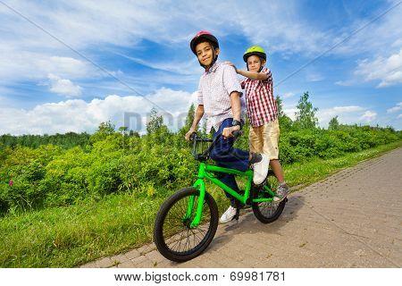 Two boys riding same bike and both stand