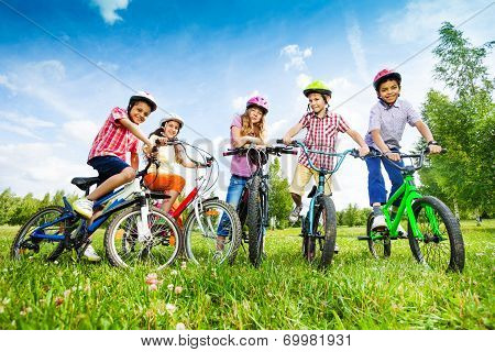 Children in colorful helmets hold their bikes