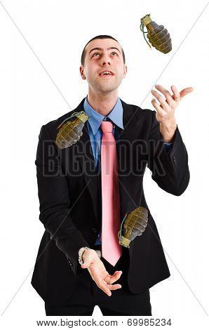 Business man juggling hand grenades