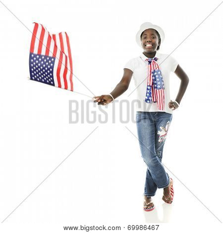 An attractive African American tween happily wearing her country's colors while waving the American flag.  On a white background.  Motion blur on flag.