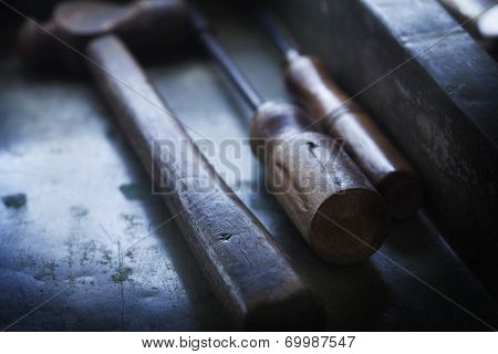 Handles of  old hand tools, Hammer and screw driver and an awl.