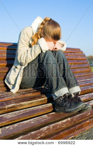 blonde woman in a depression sits on a bench