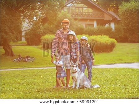Dad And His Two Daughters In Park With Dog Husky Spend Fun Time.